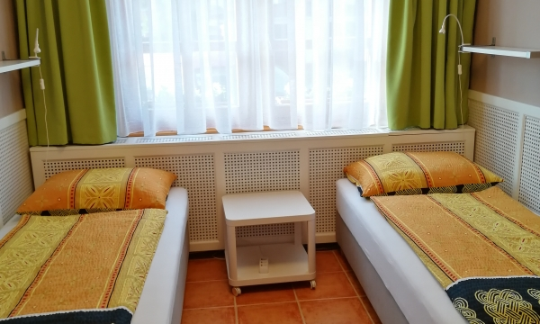 Szimpla ágyak, a szobában szekrény és olvasólámpa.